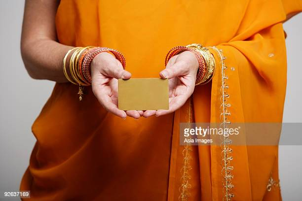 cropped shot of woman wearing sari holding credit card
