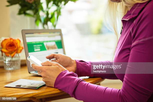 cropped shot of woman working in kitchen using smartphone - heshphoto stock pictures, royalty-free photos & images