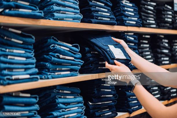 cropped shot of woman's hand selecting a pair of trousers from the display shelf while shopping in a clothing store in the city - calças de ganga imagens e fotografias de stock