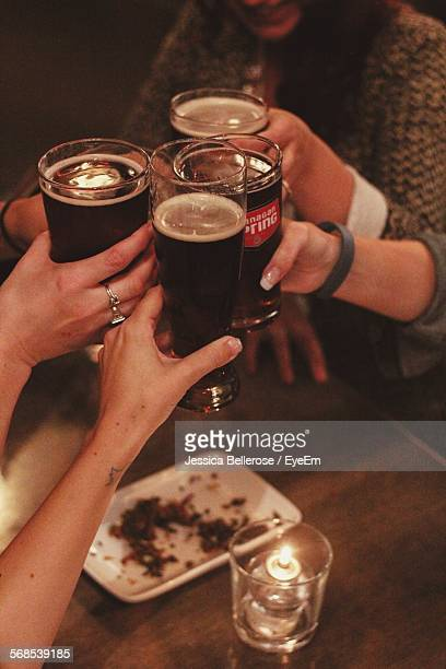 Cropped Shot Of Women Toasting Beer In Restaurant