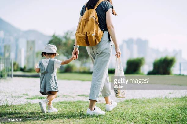 cropped shot of young asian mother carrying groceries with cotton mesh eco bag. walking hand in hand with little daughter across parkland after grocery shopping together. zero waste concept - hong kong stock pictures, royalty-free photos & images