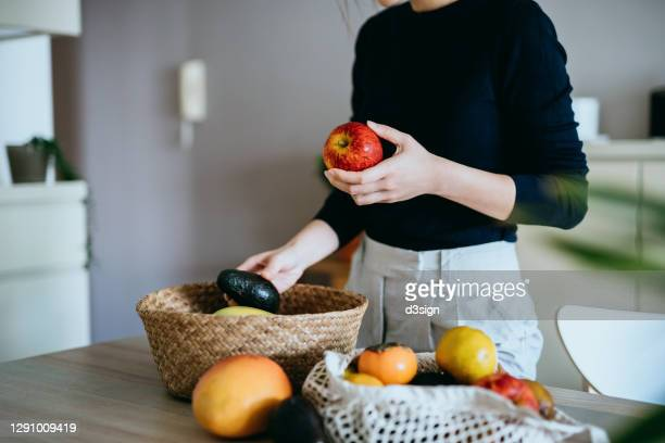 cropped shot of young asian woman coming home from grocery shopping, unpacking and organizing fresh and healthy organic fruits and veggies from a reusable bag to a rattan basket on the table. responsible shopping, zero waste, sustainable lifestyle concept - vegetable stock pictures, royalty-free photos & images