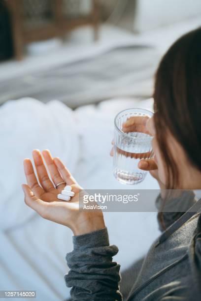 cropped shot of young asian woman lying in bed and feeling sick, taking medicines in hand with a glass of water - anti depressant stock pictures, royalty-free photos & images