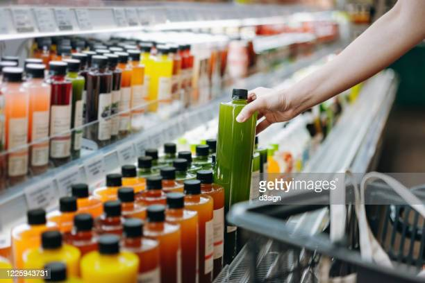 cropped shot of young asian woman shopping for fresh fruit juice from refrigerated shelves in supermarket and putting a bottle of fresh squeezed orange juice into cotton mesh eco bag in a shopping cart. zero waste concept - juice drink stock pictures, royalty-free photos & images