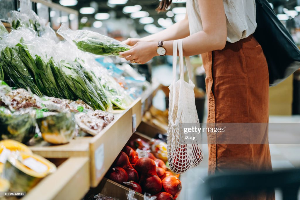 Cropped shot of young Asian woman shopping for fresh organic groceries in supermarket. She is shopping with a cotton mesh eco bag and carries a variety of fruits and vegetables. Zero waste concept : ストックフォト