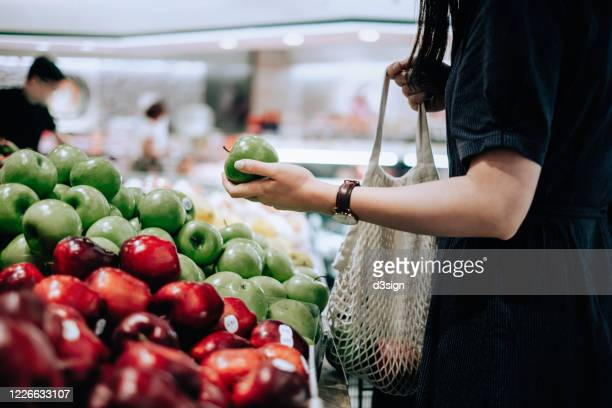 cropped shot of young asian woman shopping for fresh organic groceries in supermarket. she is shopping with a cotton mesh eco bag and carries a variety of fruits and vegetables. zero waste concept - freshness fotografías e imágenes de stock
