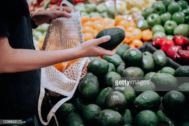 cropped shot of young asian woman shopping for fresh organic groceries in supermarket. she is shopping with a cotton mesh eco bag and carries a variety of fruits and vegetables. zero waste concept - choosing stock pictures, royalty-free photos & images