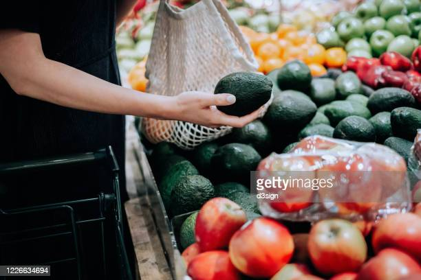cropped shot of young asian woman shopping for fresh organic groceries in supermarket. she is shopping with a cotton mesh eco bag and carries a variety of fruits and vegetables. zero waste concept - produce aisle stock pictures, royalty-free photos & images