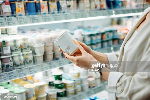cropped shot of young asian woman shopping in the dairy section of a supermarket. she is reading the nutrition label on a container of fresh organic healthy natural yoghurt - list stock pictures, royalty-free photos & images