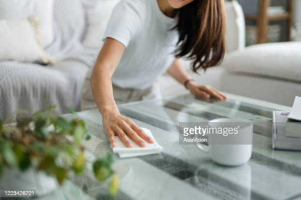 cropped shot of young asian woman tidying up the living room and wiping the coffee table surface with a cloth - clean stock pictures, royalty-free photos & images