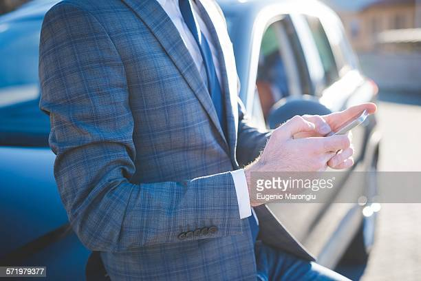 Cropped shot of young businessman leaning against car using smartphone