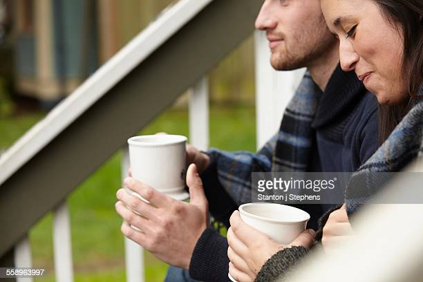 Cropped shot of young couple sitting on porch step drinking coffee