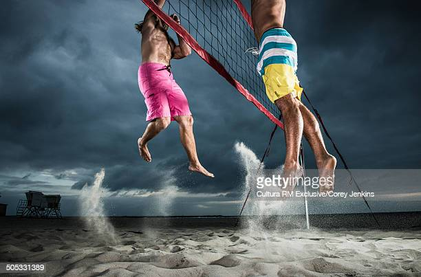 Cropped shot of young male beach volleyball players competing at volleyball net