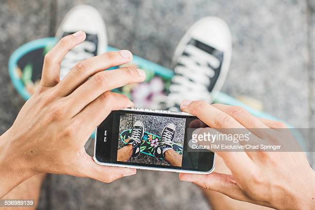 Cropped shot of young male skateboarder photographing feet on smartphone