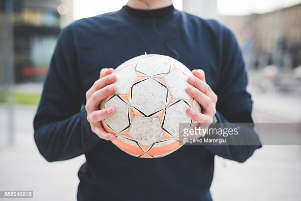 cropped shot of young man holding soccer ball - spielball stock-fotos und bilder