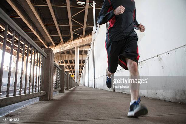 cropped shot of young man running on city bridge - heshphoto stock pictures, royalty-free photos & images