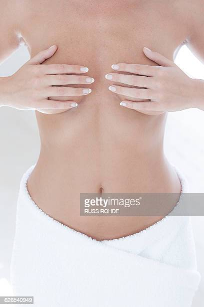 Cropped shot of young naked woman with hands touching breasts