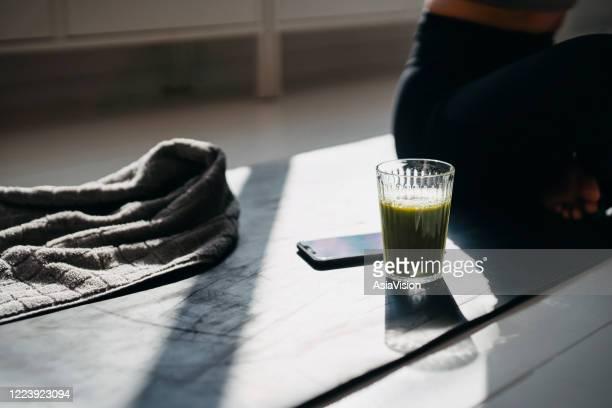 bijgesneden schot van jonge sportenvrouw die en naast een glas groene smoothie, smartphone en een handdoek in zonlicht na het uitoefenen thuis rust en zit - fitnessmat stockfoto's en -beelden