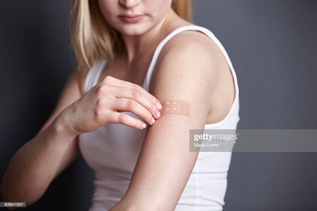 Cropped shot of young woman applying adhesive plaster to her own arm : ストックフォト