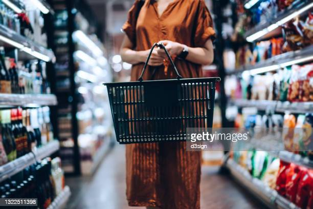 cropped shot of young woman carrying a shopping basket, standing along the product aisle, grocery shopping for daily necessities in supermarket - shop stock pictures, royalty-free photos & images