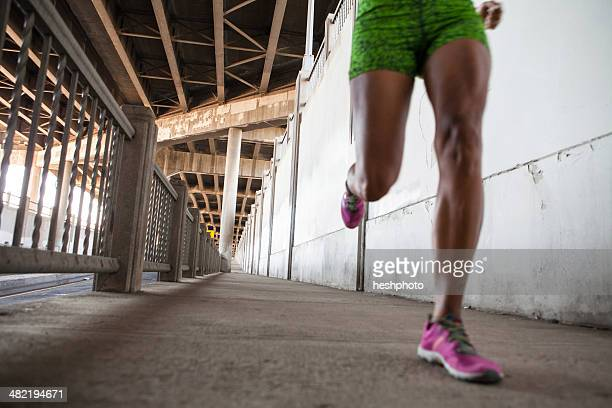 cropped shot of young woman running on city bridge - heshphoto stock pictures, royalty-free photos & images