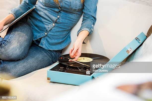Cropped shot of young woman sitting on sofa listening to vintage record player