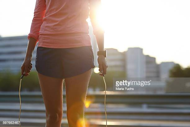 Cropped shot of young woman training with skipping rope on rooftop