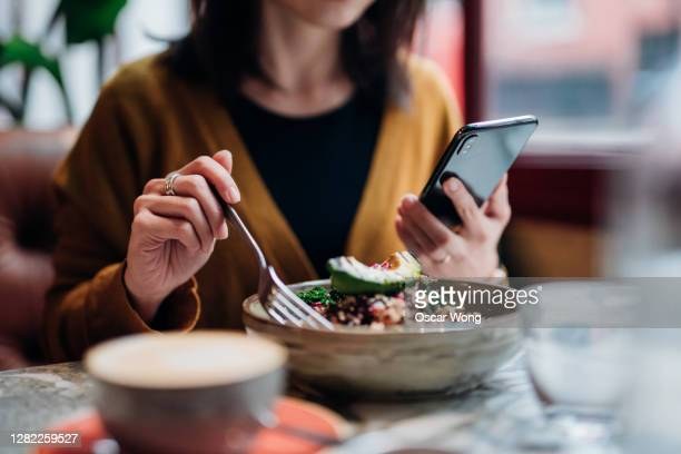 cropped shot of young woman using smart phone while eating salad in the restaurant - eating stock pictures, royalty-free photos & images