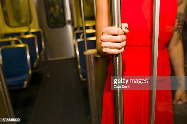 Cropped shot of young woman wearing red dress on subway train