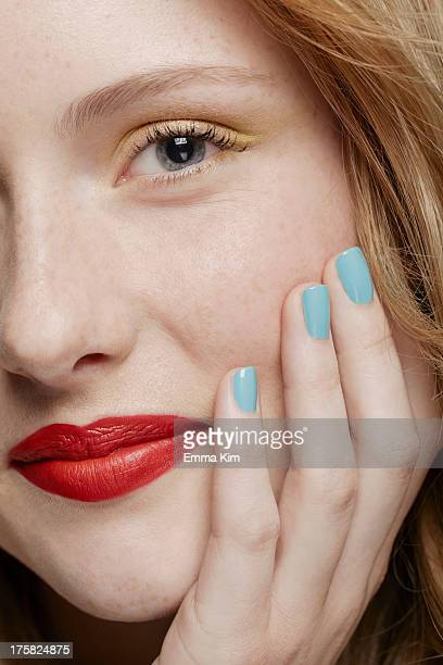 cropped shot of young woman with curly red hair wearing make up, hand on chin - マニキュア液 ストックフォトと画像