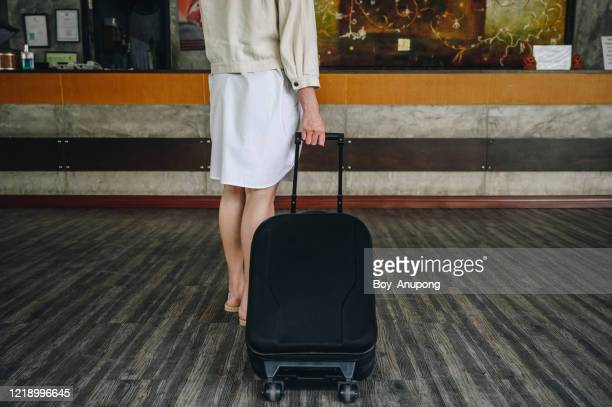 cropped shot of young woman with suitcase walking to the hotel lobby for check-in her room. - guest stock pictures, royalty-free photos & images