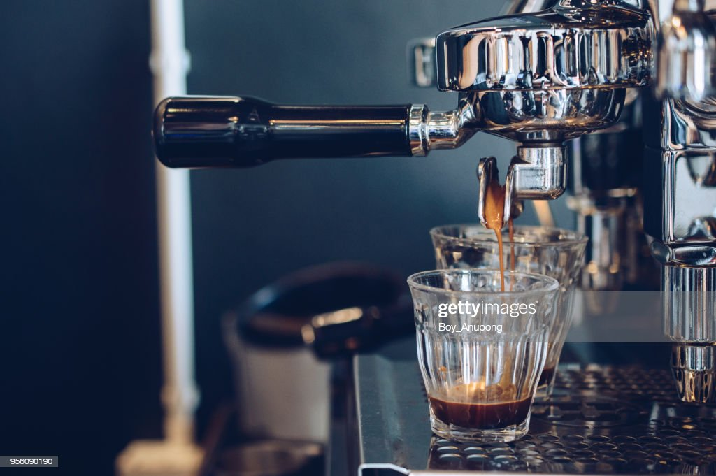 Cropped shot view of espresso pouring from coffee machine. Professional coffee brewing. : Stock Photo