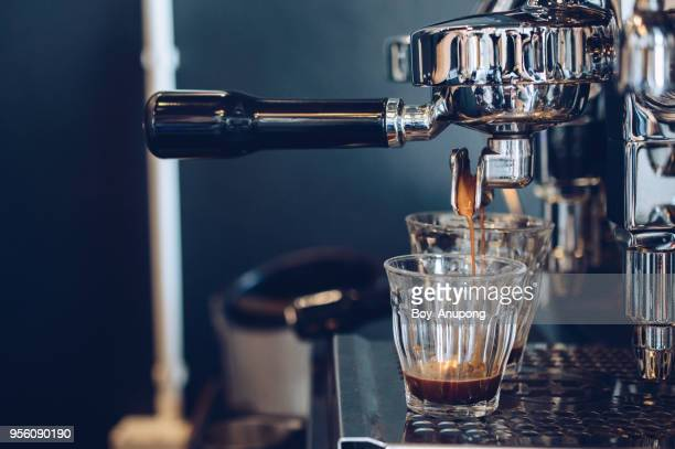 cropped shot view of espresso pouring from coffee machine. professional coffee brewing. - coffee maker stock pictures, royalty-free photos & images