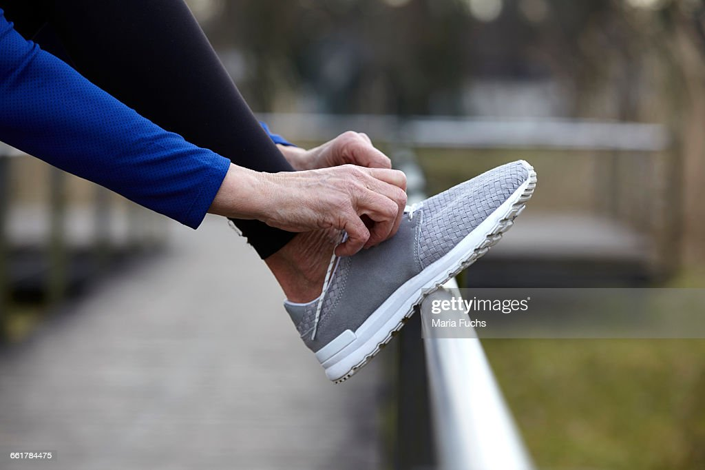Cropped side view of woman leg raised on railings tying shoelace : ストックフォト