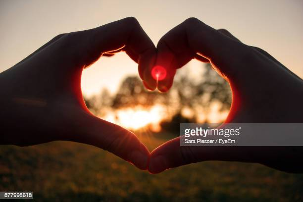 Cropped Silhouette Hands Couple Making Heart Shape Against Sky During Sunset