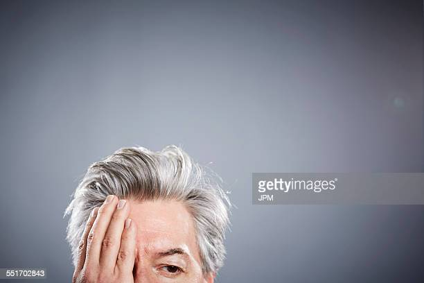 Cropped studio portrait of mature businessman with hand covering eye
