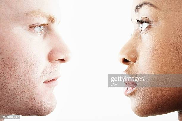 cropped studio portrait of young couple face to face in profile - angesicht zu angesicht stock-fotos und bilder