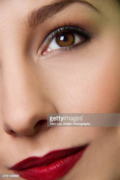 Cropped studio portrait of young woman's eye and lips