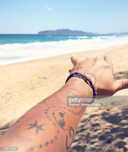 cropped tattooed hand of woman gesturing at beach - bracelet stock pictures, royalty-free photos & images