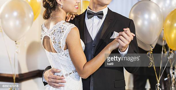 Cropped teenage couple at prom dancing