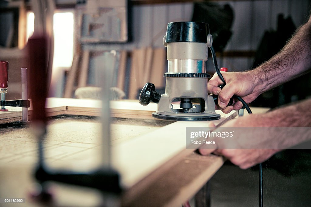 A cropped view of adult, male carpenter working with tools in his wood shop : Stock Photo