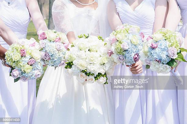 Cropped view of bride and bridesmaids side by side holding flower bouquets