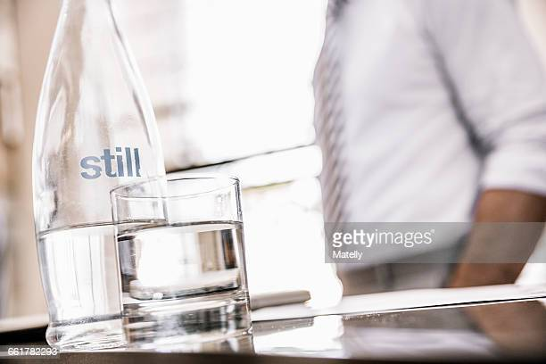 Cropped view of businessmans mid section with glass bottle of water and drinking glass