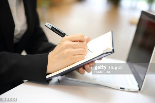 cropped view of businesswoman taking notes at desk - handbook stock photos and pictures