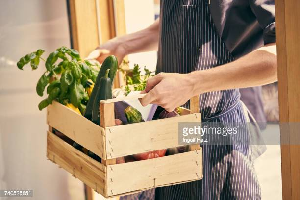 cropped view of chef carrying crate of vegetables - holzkiste stock-fotos und bilder