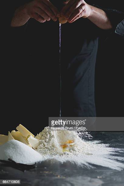 Cropped View Of Chef Cracking Egg Onto Flour