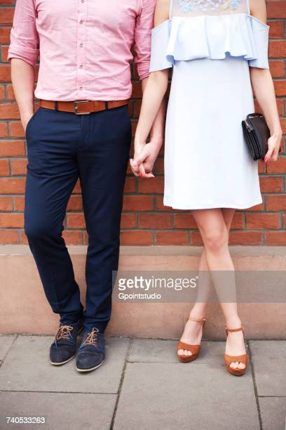 cropped view of couple holding hands in front of brick wall - historical romance stock photos and pictures