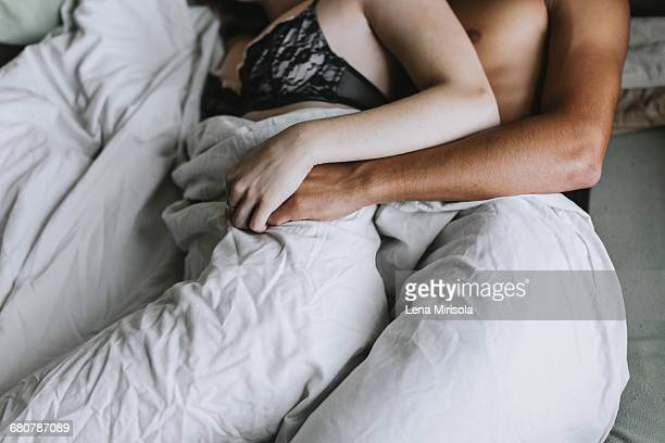Cropped view of couple spooning in bed