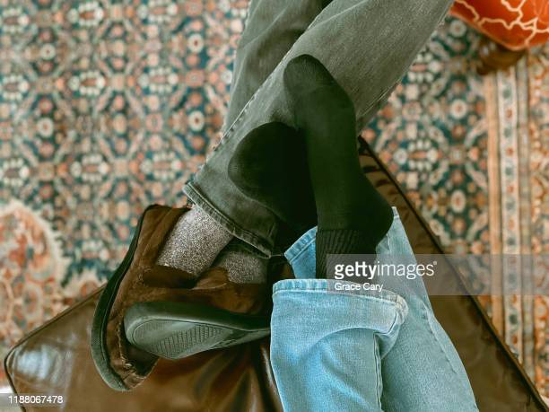 cropped view of couple's feet on ottoman - denim stock pictures, royalty-free photos & images