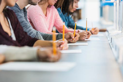 Cropped view of group of teenagers taking a test 535847793